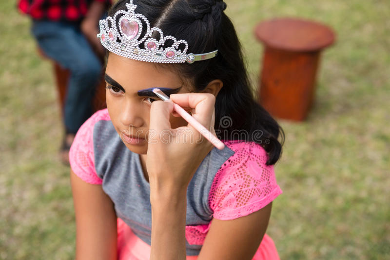 Cropped hand on mother applying face paint on girl wearing crown stock photography