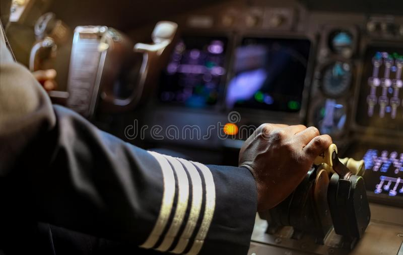 Cropped Hands of African Pilot flying a commercial airplane. Cockpit view close up of hands stock photos
