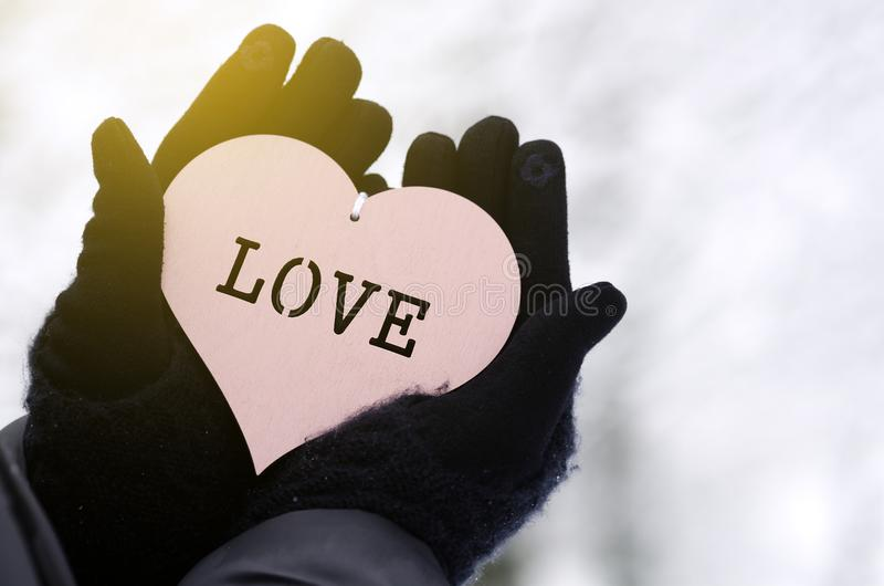 Cropped hands in gloves hold a heart with the inscription love royalty free stock images