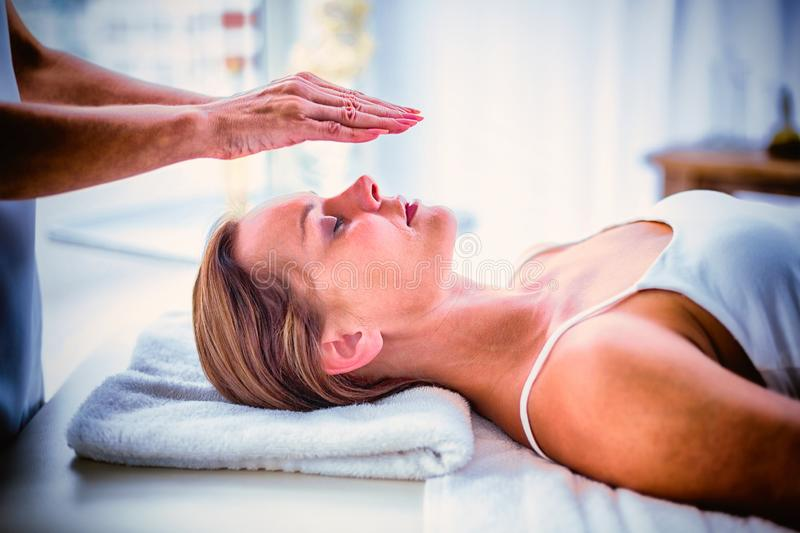 Cropped hands of therapist performing reiki on woman stock images