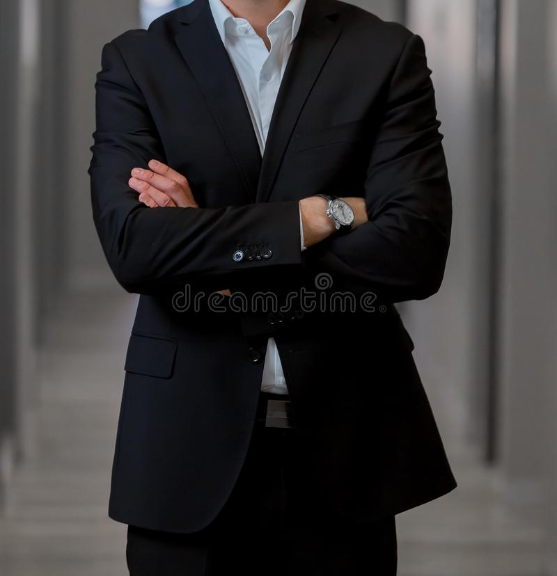 Cropped head Man standing in a smart suit with folded arms. Cropped head Man standing in a smart suit with arms folded royalty free stock photo