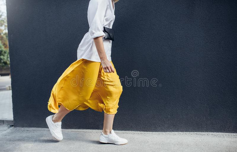 Cropped horizontal image of attractive woman in beautiful yellow skirt runing on the street. Caucasian female fashion model stock photo