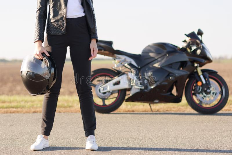 Cropped horizontal shot of female biker dressed in black leather jacket, trousers and white sneakers, holds helmet, stands on asph stock image