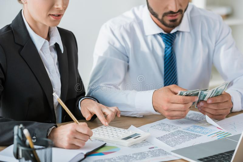Cropped image of accountants calculating dollars. In office royalty free stock images
