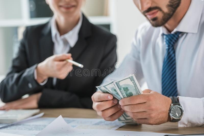 Cropped image of accountants sitting with dollars. In office stock photos