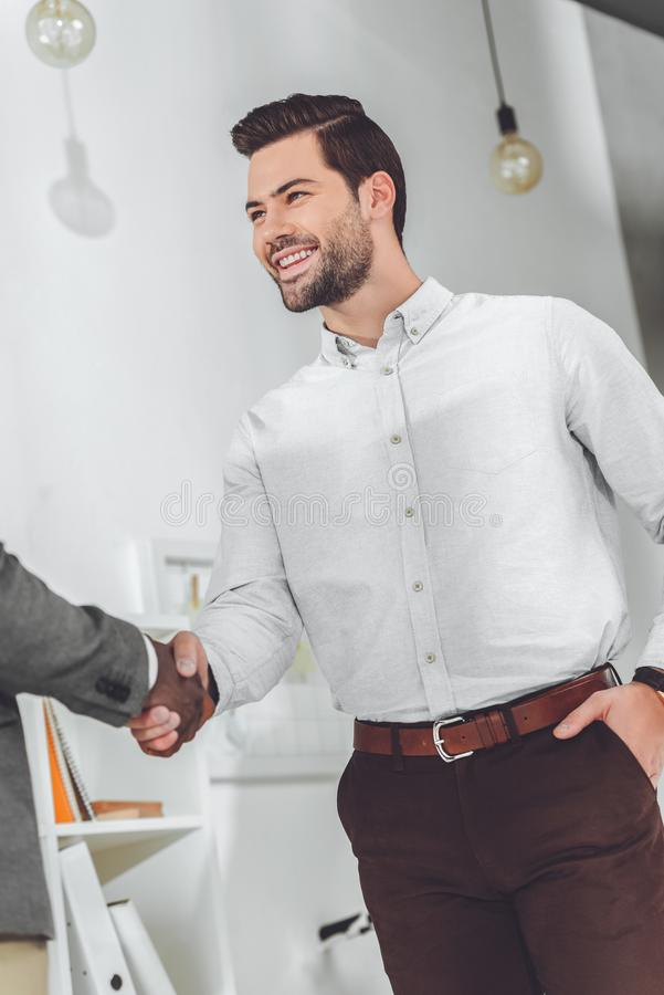 Cropped image of african american and caucasian businessmen. Shaking hands stock illustration