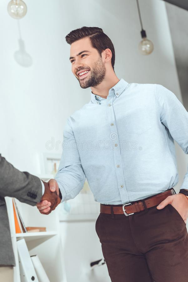 Cropped image of african american and caucasian businessmen. Shaking hands vector illustration