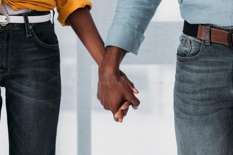 cropped image of african american couple holding hands at home stock images