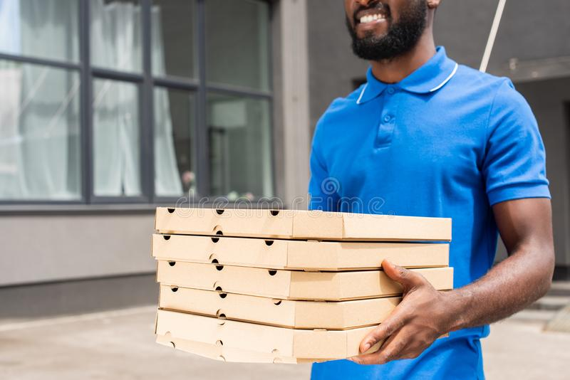 Cropped image of african american delivery man. Carrying pizza boxes stock photo