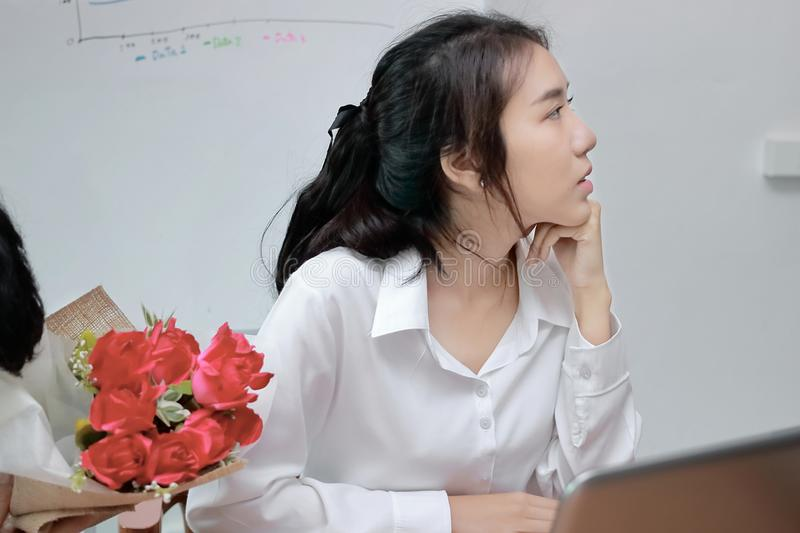 Cropped image of angry Asian woman refuses a bouquet of red roses from business man in office. Disappointed love concept. Cropped image of angry Asian woman royalty free stock photography