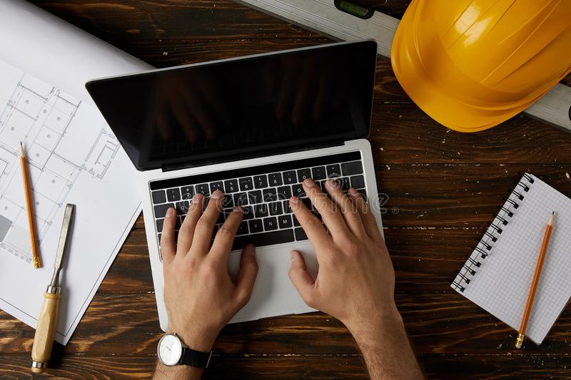 Cropped image of architect typing on laptop at table with chisel, spirit level, protective helmet, blueprint, textbook and pencils royalty free stock photo