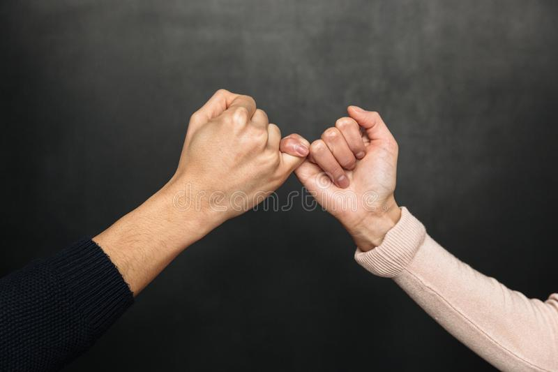 Cropped image of Asian couple holding pinkies to each other stock images
