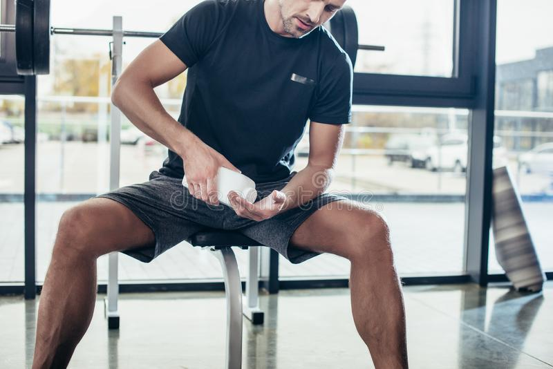 Cropped image of athletic man applying talcum powder on hands before training. In gym royalty free stock photos