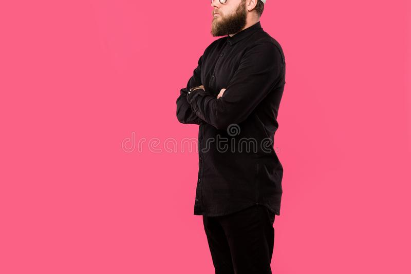 Cropped image of bearded hipster man posing with crossed arms isolated. On pink stock photography