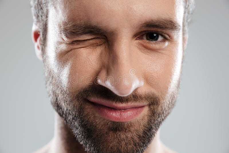 Cropped image of a bearded mans face winking. Isolated over white background royalty free stock photo