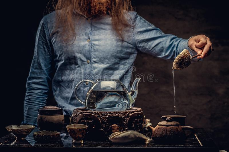 Cropped image of a bearded redhead male in a blue shirt preparing tea using a handmade tea set. royalty free stock images