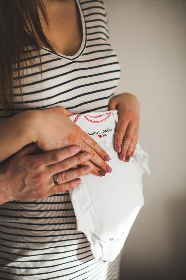 Cropped image of a beautiful pregnant woman and her handsome husband hugging the tummy and holds children`s clothes. baby theme. stock images