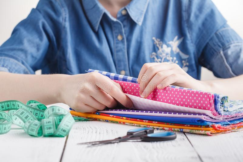 Cropped image of beautiful young designer working with sketches and measure tape in dressmaking salon royalty free stock photo