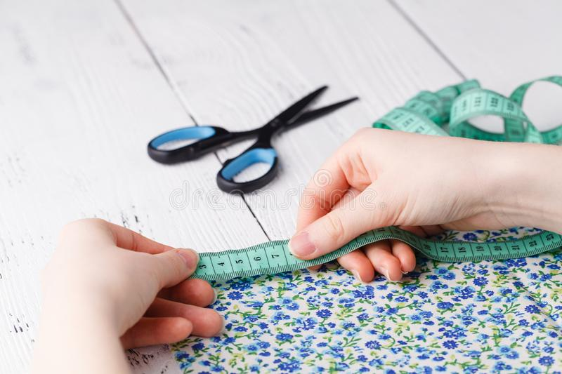 Cropped image of beautiful young designer working with sketches and measure tape in dressmaking salon stock photo