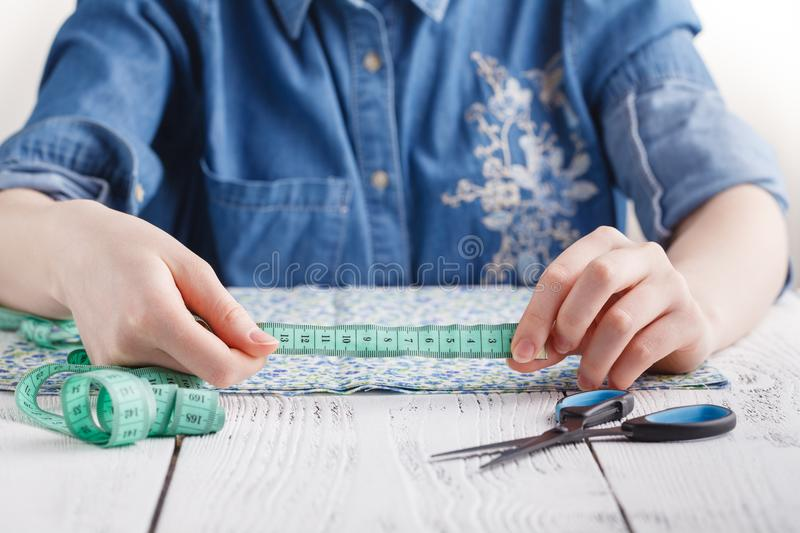 Cropped image of beautiful young designer working with sketches and measure tape in dressmaking salon royalty free stock images