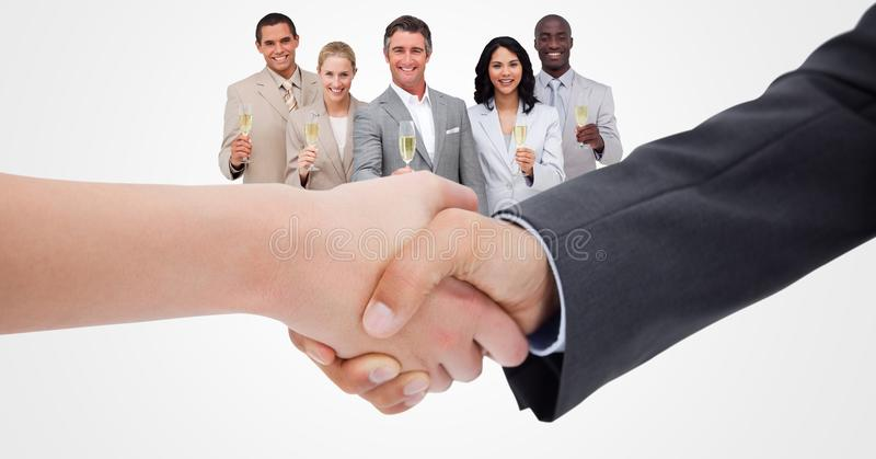 Cropped image of business people doing handshake with employees holding champagne in background stock photo