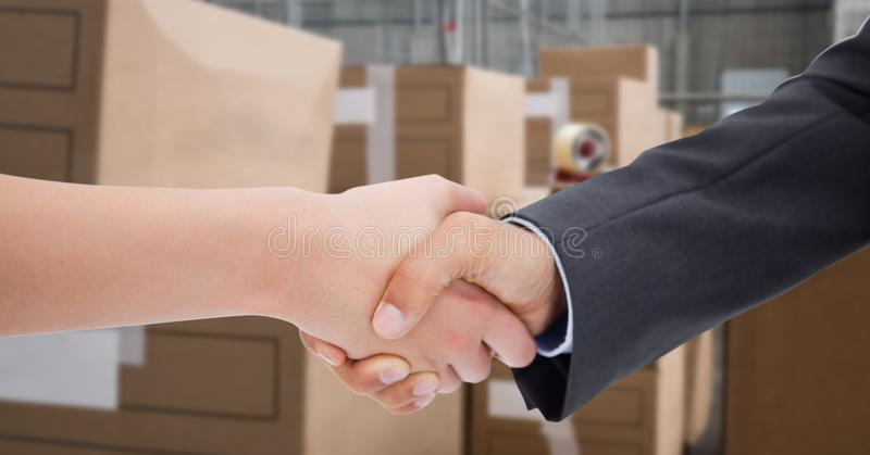 Cropped image of business people doing handshake in warehouse stock photography