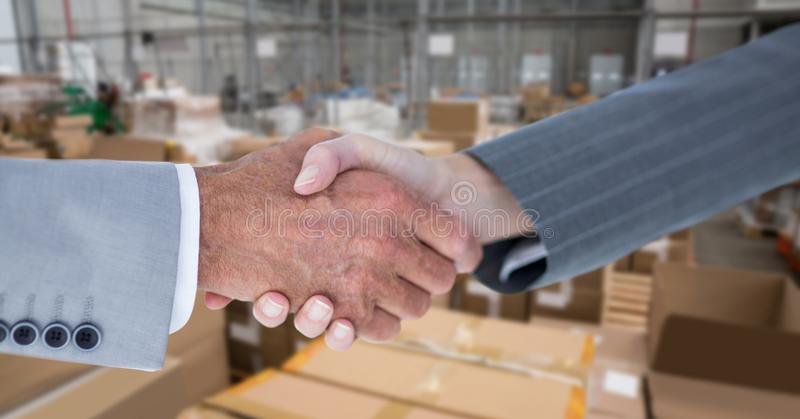 Cropped image of business people doing handshake in warehouse royalty free stock photography