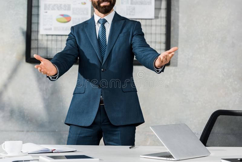 Cropped image of businessman gesturing and standing with open arms. In office royalty free stock image
