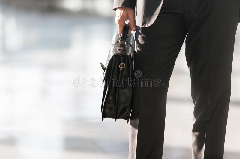 Cropped image of businessman holding briefcase bag in airport. Photo of businessman holding briefcase bag in airport stock image