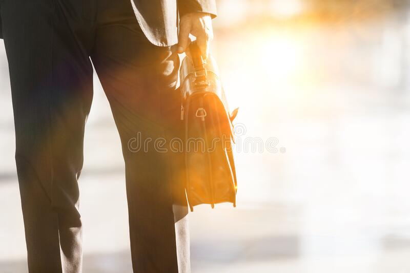 Cropped image of businessman holding briefcase bag in airport. With yellow lens flare royalty free stock photo