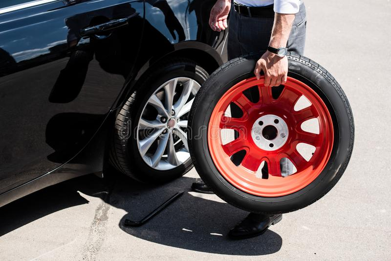 cropped image of businessman holding tire for wheel replacement royalty free stock images