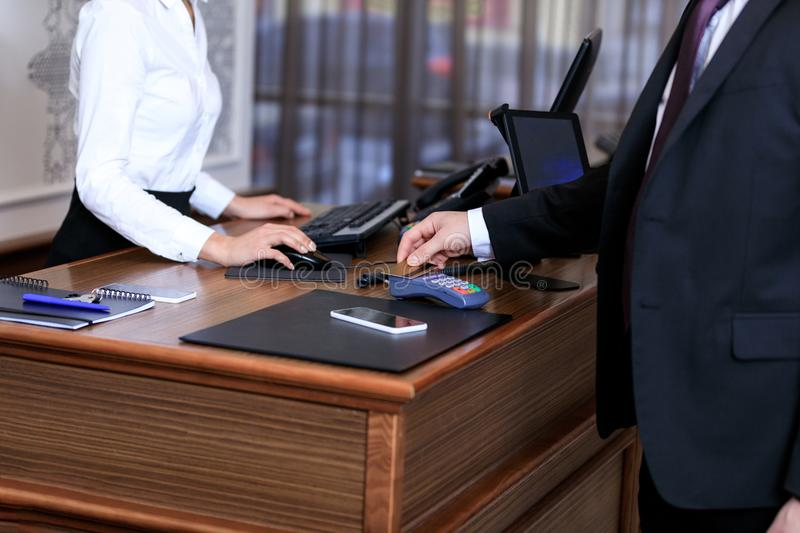 Cropped image of businessman paying with credit card. In hotel stock photo