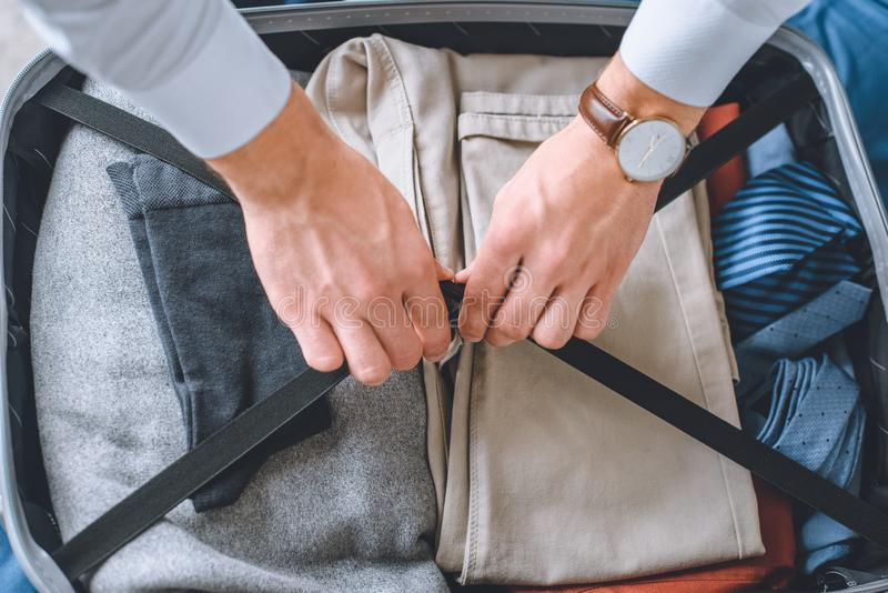 Cropped image of businessman with wristwatch packing luggage. In suitcase stock photography