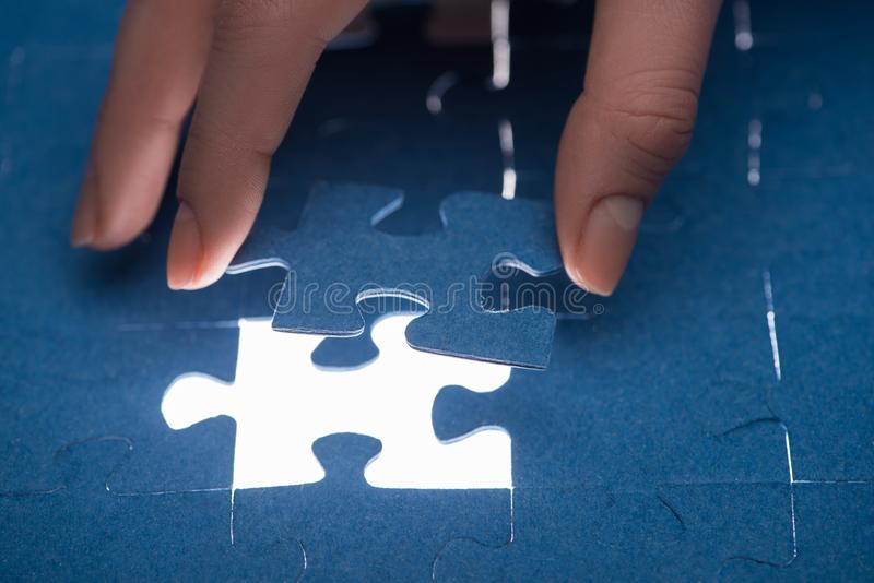 cropped image of businesswoman inserting last missing puzzle, royalty free stock photo