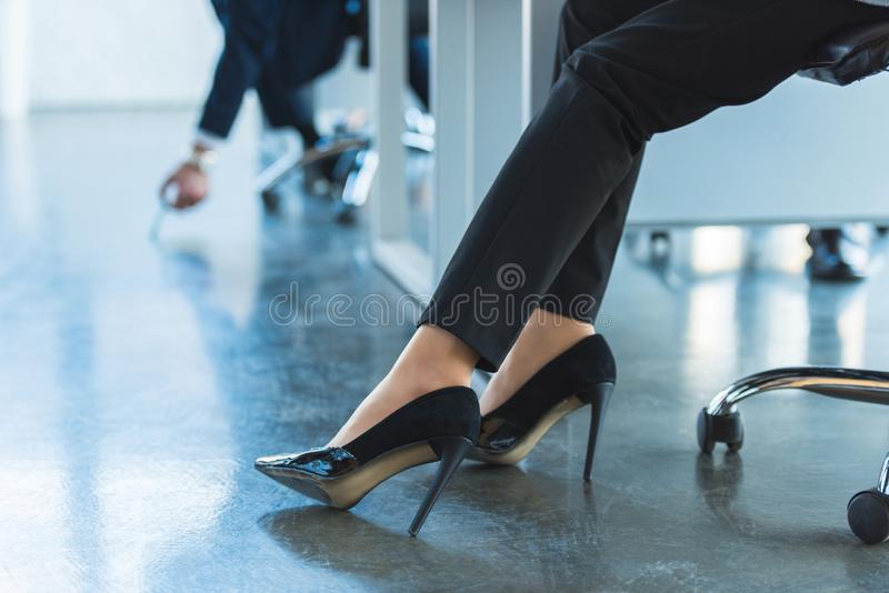 Cropped image of businesswoman sitting on chair. In office royalty free stock photography