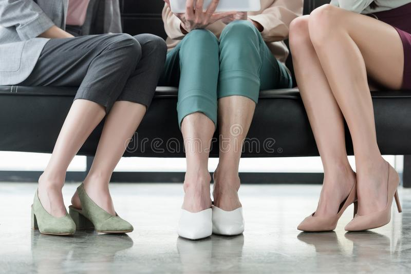Cropped image of businesswomen sitting on sofa. In office royalty free stock photos