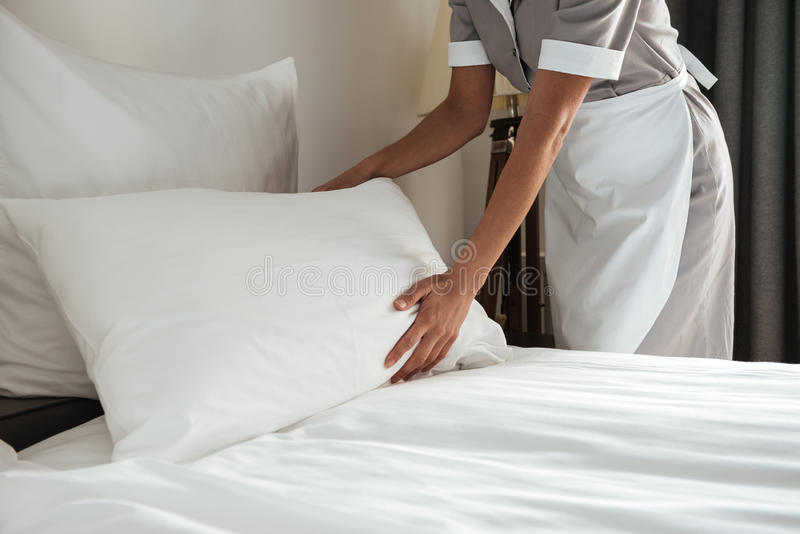Cropped image of a chambermaid making bed in hotel room. Cropped image of a female chambermaid making bed in hotel room royalty free stock images