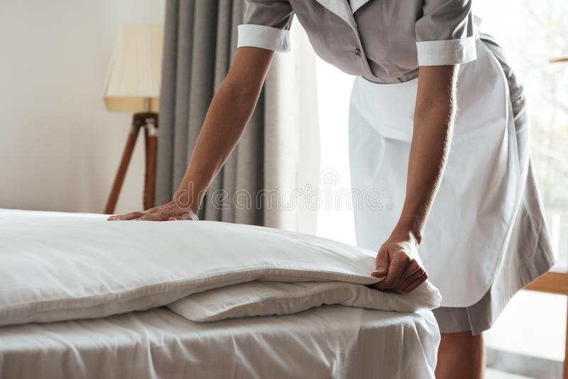 Cropped image of a chambermaid making bed in hotel room. Cropped image of a female young maid making bed in hotel room royalty free stock images