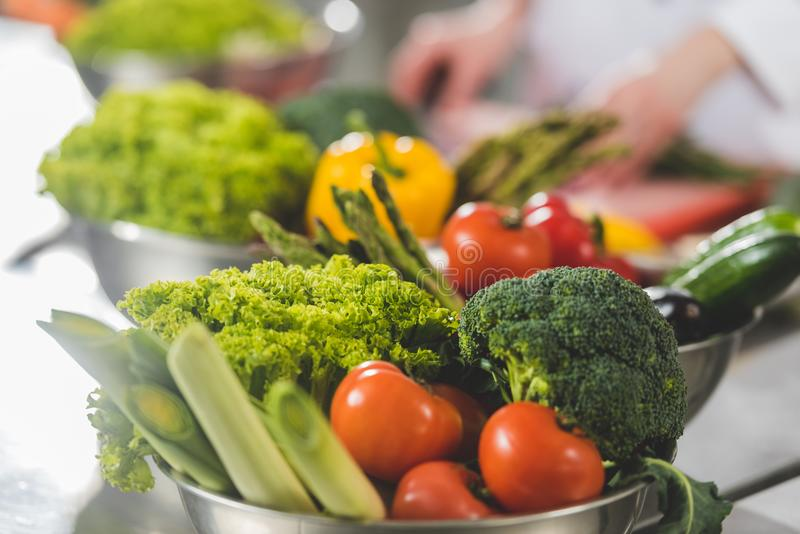 Cropped image of chef cooking at restaurant kitchen with ripe vegetables. On foreground royalty free stock photo