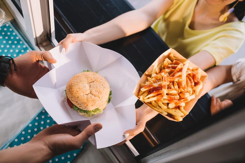 cropped image of chef giving burger and french fries to customers from food truck royalty free stock images