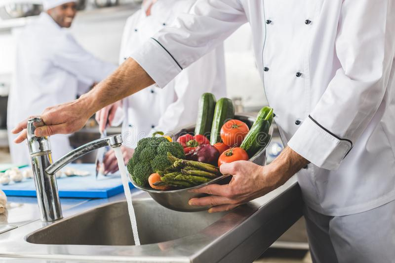 Cropped image of chef washing vegetables. At restaurant kitchen stock image