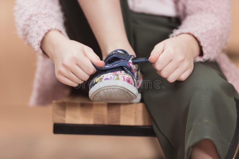 cropped image of child tying lace on sneaker while stock photography