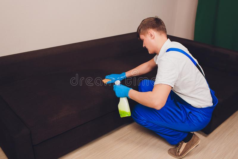 Cropped image. Cleaning concept. Male hand in blue protective gloves cleaning sofa couch in the room. stock photography