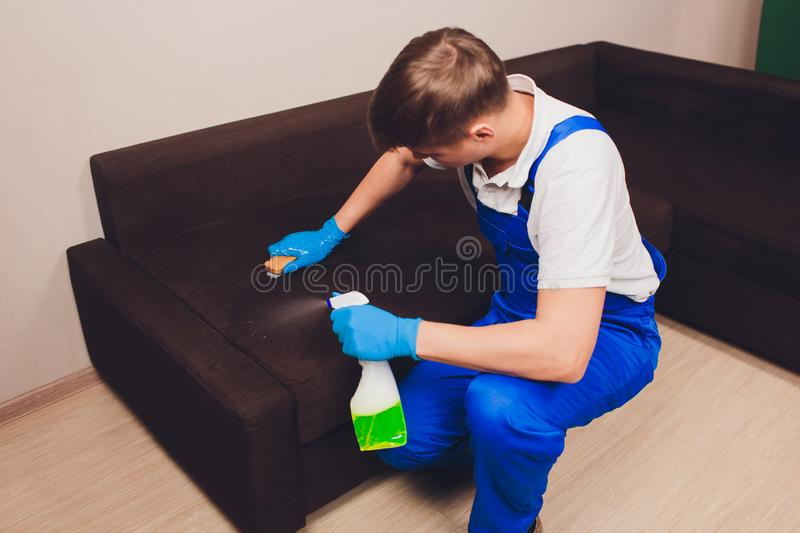 Cropped image. Cleaning concept. Male hand in protective gloves cleaning sofa couch in the room. Cropped image. Cleaning concept. Male hand in protective gloves royalty free stock photo