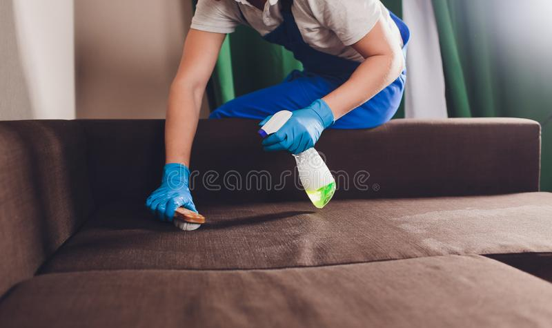 Cropped image. Cleaning concept. Male hand in protective gloves cleaning sofa couch in the room. Cropped image. Cleaning concept. Male hand in protective gloves royalty free stock photos