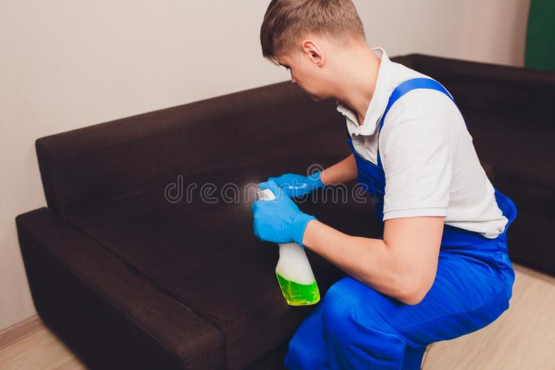 Cropped image. Cleaning concept. Male hand in protective gloves cleaning sofa couch in the room. stock image