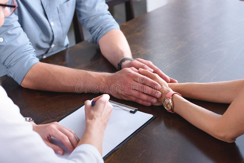 Cropped image of couple holding hands of each other while female counselor writing in clipboard at table. In office stock images