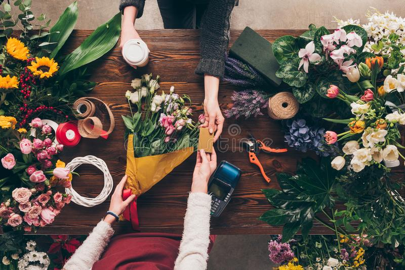 Cropped image of customer giving florist credit card to pay. For bouquet royalty free stock photography
