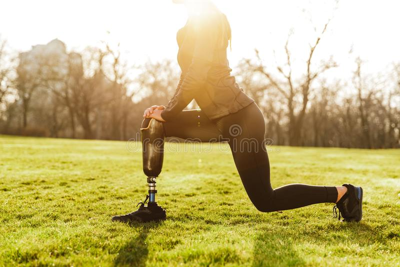 Cropped image of disabled athletic girl in black sportswear, doing lunges and stretching prosthetic leg on grass royalty free stock images