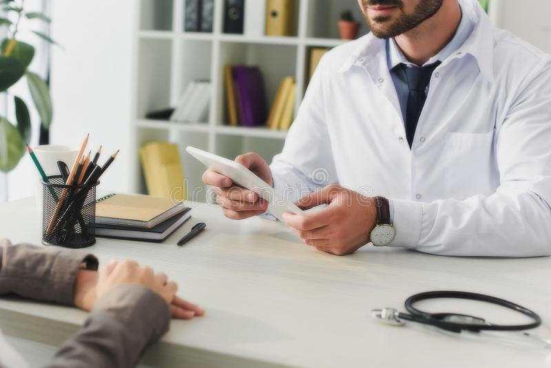 Cropped image of doctor holding tablet. In clinic royalty free stock image